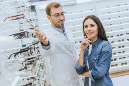 Photo for Cheerful male oculist pointing by hand at shelves with eyeglasses to woman in optics - Royalty Free Image