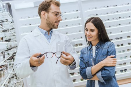male optometrist showing eyeglasses to young woman in ophthalmic shop