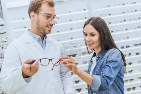 selective focus of male optometrist showing eyeglasses to smiling woman in optica