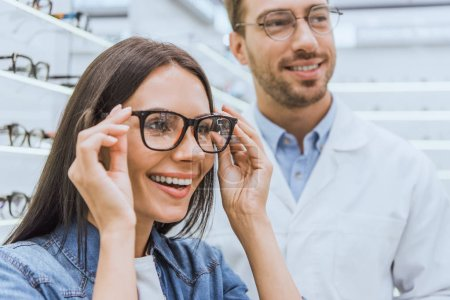portrait of smiling woman choosing eyeglasses while male optometrist standing near in optics