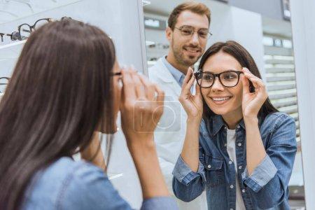 Photo pour Vue arrière de la femme gaie choisissant des lunettes et regardant le miroir tandis que l'optométriste masculin debout près de l'optica - image libre de droit