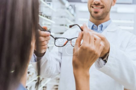 Photo for Partial view of male oculist giving eyeglasses to woman in ophthalmic shop - Royalty Free Image