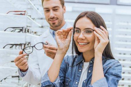 Photo pour Belle femme souriante qui choisit des lunettes tandis que l'oculiste masculin se tient près d'une autre lunette dans la boutique ophtalmique - image libre de droit