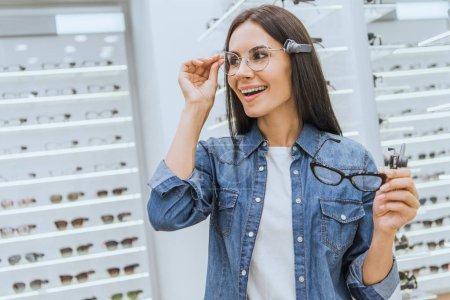 smiling attractive woman choosing eyeglasses in optics