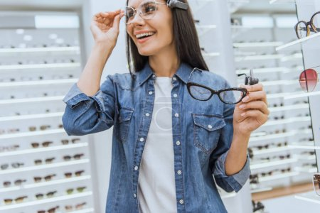 selective focus of happy young woman choosing eyeglasses in ophthalmic shop
