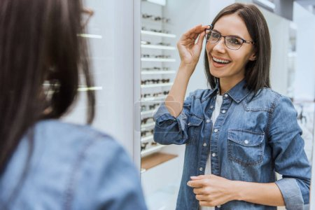 partial view of beautiful happy woman choosing eyeglasses and looking at mirror in optica