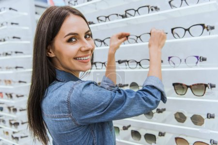 portrait of smiling young woman taking eyeglasses from shelves and looking at camera in ophthalmic shop