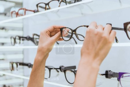 Photo for Partial view of optician taking glasses from shelf in ophthalmic shop - Royalty Free Image
