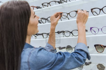 side view of attractive young woman taking eyeglasses from shelves in optics