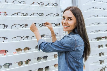 beautiful young woman taking eyeglasses from shelves in optica