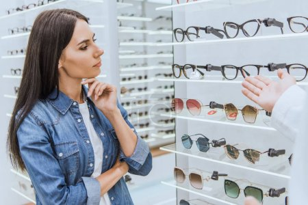 thoughtful woman looking at shelves while oculist pointing by hand at eyeglasses to her in optica