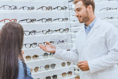 smiling male oculist pointing by hand at shelves with eyeglasses to woman in optics
