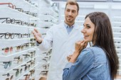 attractive happy woman standing near with male oculist pointing by hand at shelves with eyeglasses in optica