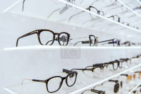 selective focus of white shelves with trendy glasses in ophthalmic shop