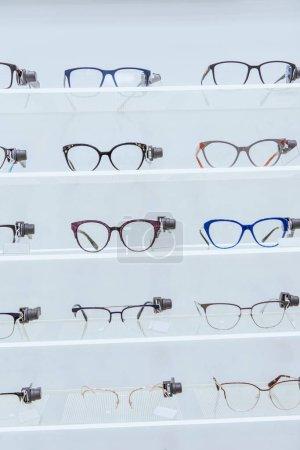 Photo pour Étagères blanches avec des lunettes élégantes dans optica - image libre de droit
