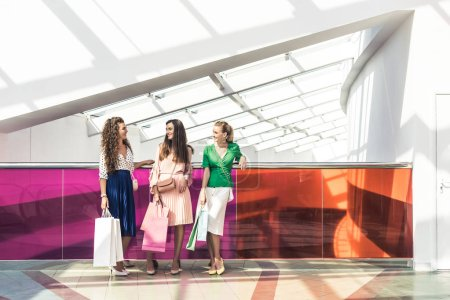 Photo for Full length view of stylish girls holding paper bags and talking in shopping mall - Royalty Free Image