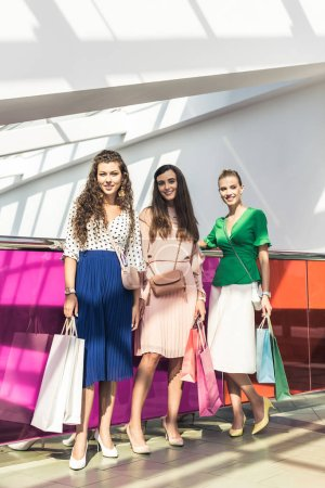 beautiful fashionable girls holding paper bags and smiling at camera while standing together in shopping mall