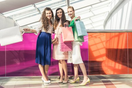 fashionable young women holding paper bags and smiling at camera while standing together in shopping mall