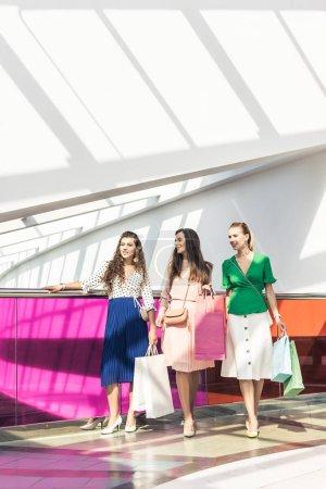 Photo pour Sourire des filles à la mode maintenant des sacs en papier et en regardant loin du centre commercial - image libre de droit