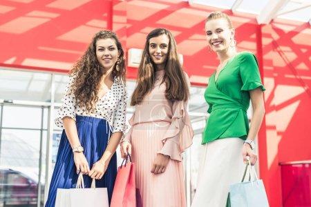 Photo pour Vue à angle bas de belles jeunes femmes élégantes tenant des sacs en papier et souriant à la caméra dans le centre commercial - image libre de droit