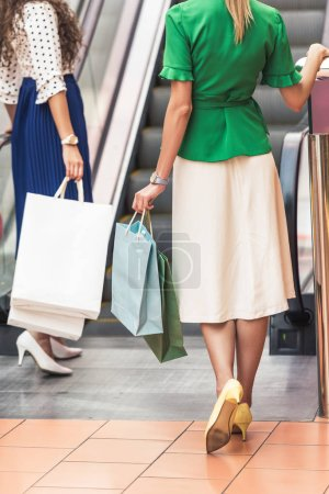 cropped shot of stylish girls with paper bags walking in shopping mall