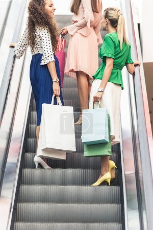 cropped shot of stylish young women holding paper bags on escalator in shopping mall