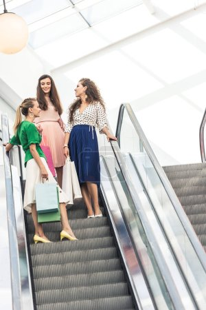 low angle view of beautiful smiling young women holding paper bags on escalator in shopping mall