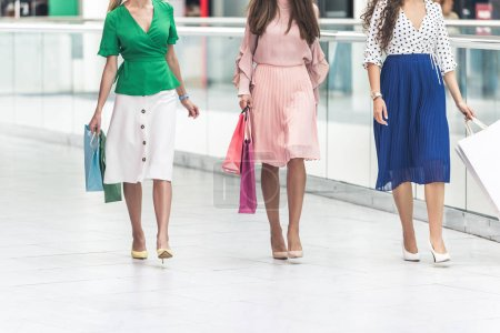 cropped shot of young women holding shopping bags and walking together in mall