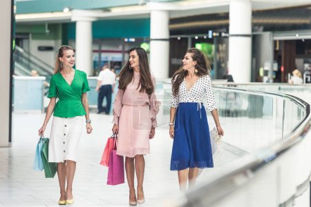 beautiful smiling young women holding shopping bags and walking together in mall