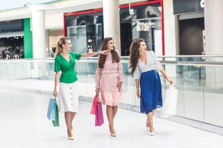 Photo pour Souriant jeunes femmes élégantes tenant des sacs en papier et regardant loin tout en marchant ensemble dans le centre commercial - image libre de droit