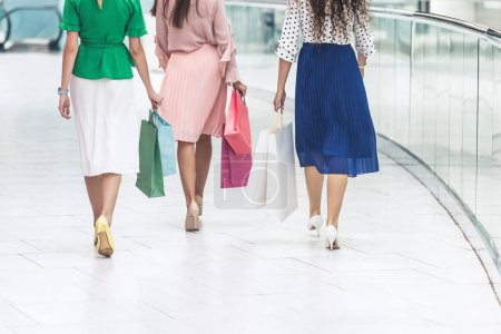 Photo for Back view of stylish girls in skirts and high heeled shoes holding paper bags and walking in shopping mall - Royalty Free Image