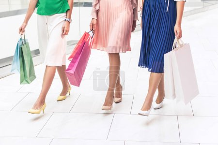 low section of stylish girls in high heeled shoes and skirts holding paper bags and walking in shopping mall