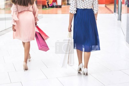 cropped shot of stylish girls holding paper bags and walking in shopping mall