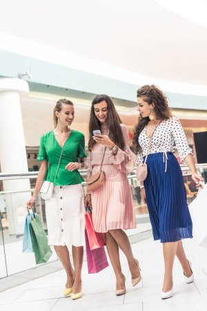 Photo for Smiling stylish girls holding paper bags and using smartphone while walking in shopping mall - Royalty Free Image