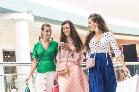 Photo for Beautiful smiling girls holding paper bags and using smartphone in shopping mall - Royalty Free Image