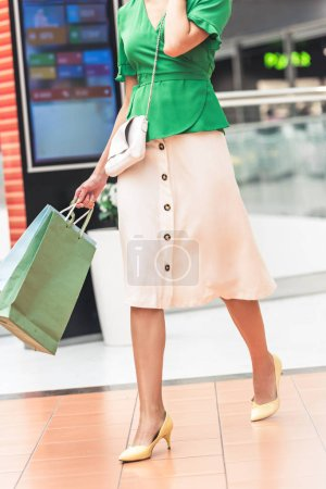 Photo for Cropped shot of stylish young woman holding paper bags and walking in shopping mall - Royalty Free Image