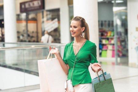 Photo pour Belle fille blonde souriante tenant des sacs en papier et regardant loin dans le centre commercial - image libre de droit