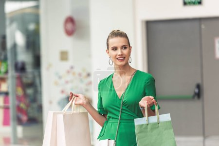 Photo for Beautiful smiling blonde girl holding shopping bags and looking away in mall - Royalty Free Image
