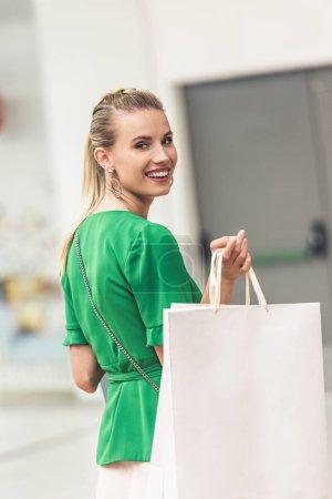 Photo pour Belle fille blonde tenant des sacs à provisions et souriant à la caméra - image libre de droit