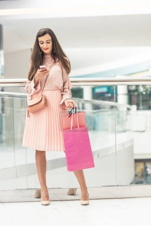 Photo for Beautiful smiling young woman holding shopping bags and using smartphone in mall - Royalty Free Image