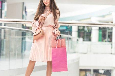 Photo pour Recadrée tir d'élégante fille tenant des sacs à provisions et à l'aide de smartphone dans centre commercial - image libre de droit