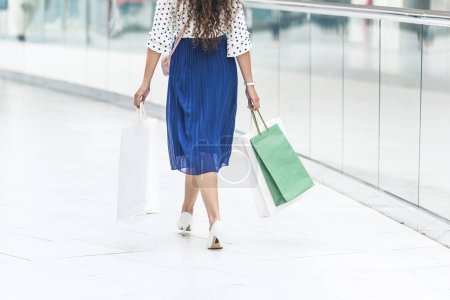 back view of girl holding paper bags and walking in shopping mall