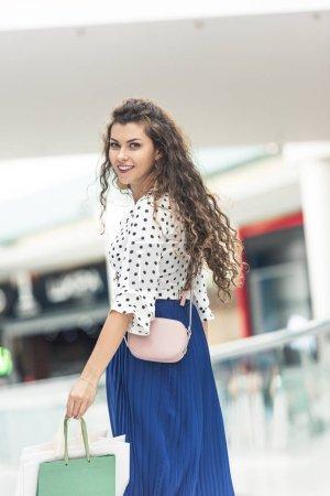 Photo pour Belle jeune femme élégante tenant des sacs à provisions et souriant à la caméra - image libre de droit