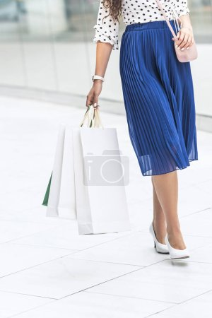 cropped shot of girl in stylish skirt and high heeled shoes holding shopping bags in mall