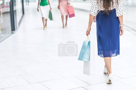 low section of stylish girls in skirts and high heeled shoes walking with shopping bags in mall