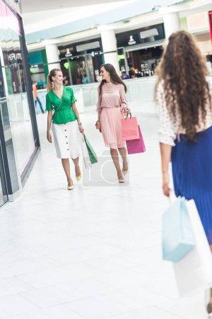 Photo pour Belles jeunes femmes à la mode tenant des sacs à provisions et marchant dans le centre commercial - image libre de droit