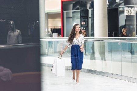 full length view of smiling stylish young woman holding shopping bags and walking in mall