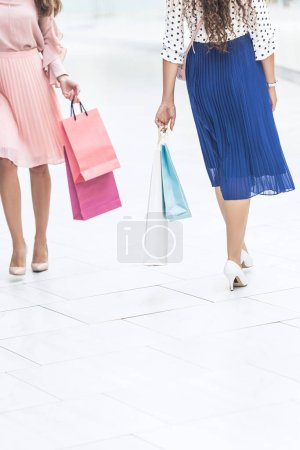cropped shot of stylish young women holding paper bags and walking in shopping mall