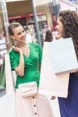 beautiful stylish girls holding shopping bags and talking in mall