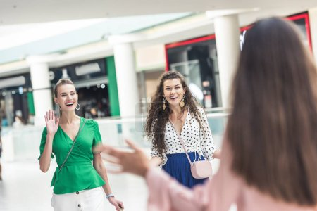 selective focus of cheerful young women greeting each other in shopping mall